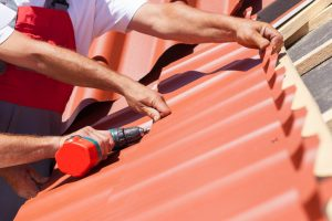 Workers on a roof with electric drill installing red metal tile on wooden house